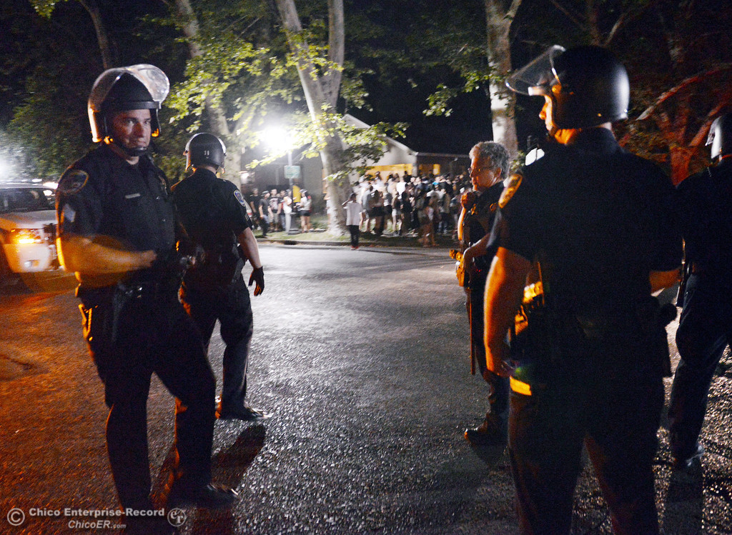 Description of . Chico Police Sgt. Curtis Prosise (left) prepares to disperse crowds as they responded to large incidents and parties in the south campus area Friday, August 23, 2013 in Chico, Calif. Police wore helmets after bottles were thrown at them.