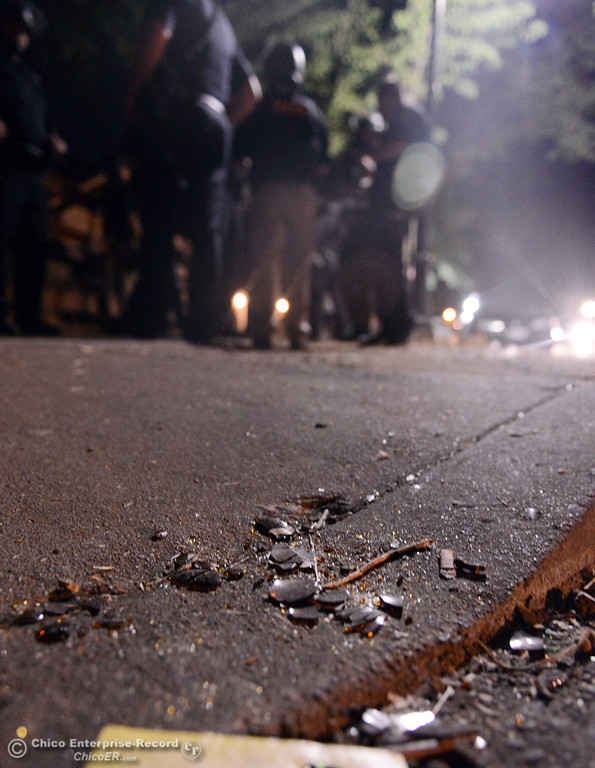 Description of . Broken glass lies on the ground after Chico Police cleared a large gathering of people at W. 6th St. and Ivy St. after trying to get to a victim of a fight in the south campus area Friday, August 23, 2013 in Chico, Calif.  Police put on helmets after bottles were thrown at them.