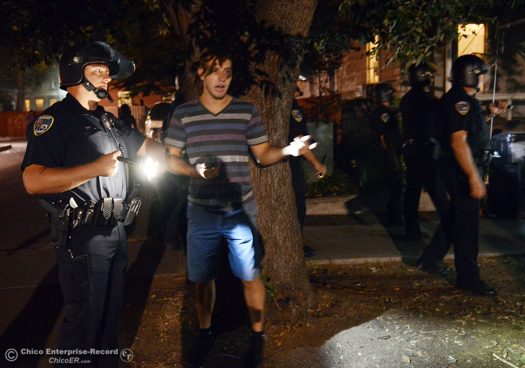 Description of . Chico Police officers clear Ivy St. near W. 6th St of large crowds as they responded to incidents in the south campus area Friday, August 23, 2013 in Chico, Calif. Police put on helmets after bottles were thrown at them.
