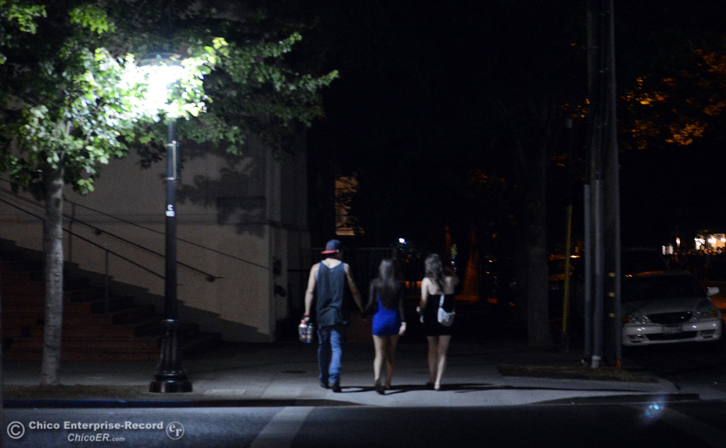 Description of . People walk along W. 4th St. under a streetlight before Chico Police responded to large incidents in the south campus area Friday, August 23, 2013 in Chico, Calif. 