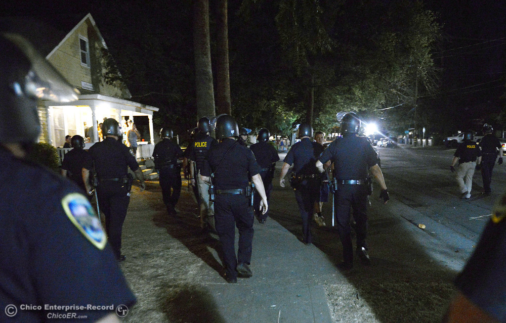 Description of . Chico Police patrol Ivy St. in the south campus area Friday, August 23, 2013 in Chico, Calif.  Police put on helmets after bottles were thrown at them.