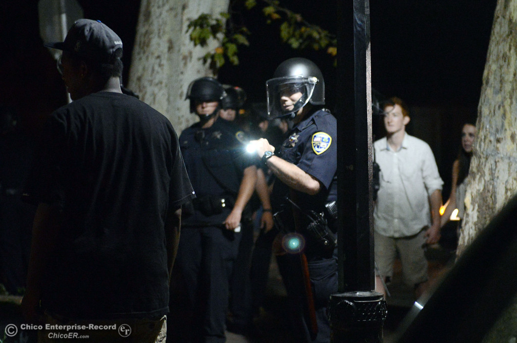 Description of . Chico Police clear a large gathering of people at W. 6th St. and Ivy St. after trying to get to a victim of a fight in the south campus area Friday, August 23, 2013 in Chico, Calif.  Police put on helmets after bottles were thrown at them.