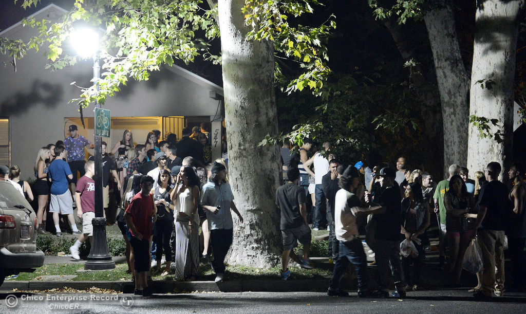 Description of . People gather at a house on the corner of 6th St. and Ivy St. as Chico Police responded to large incidents in the south campus area Friday, August 23, 2013 in Chico, Calif. 