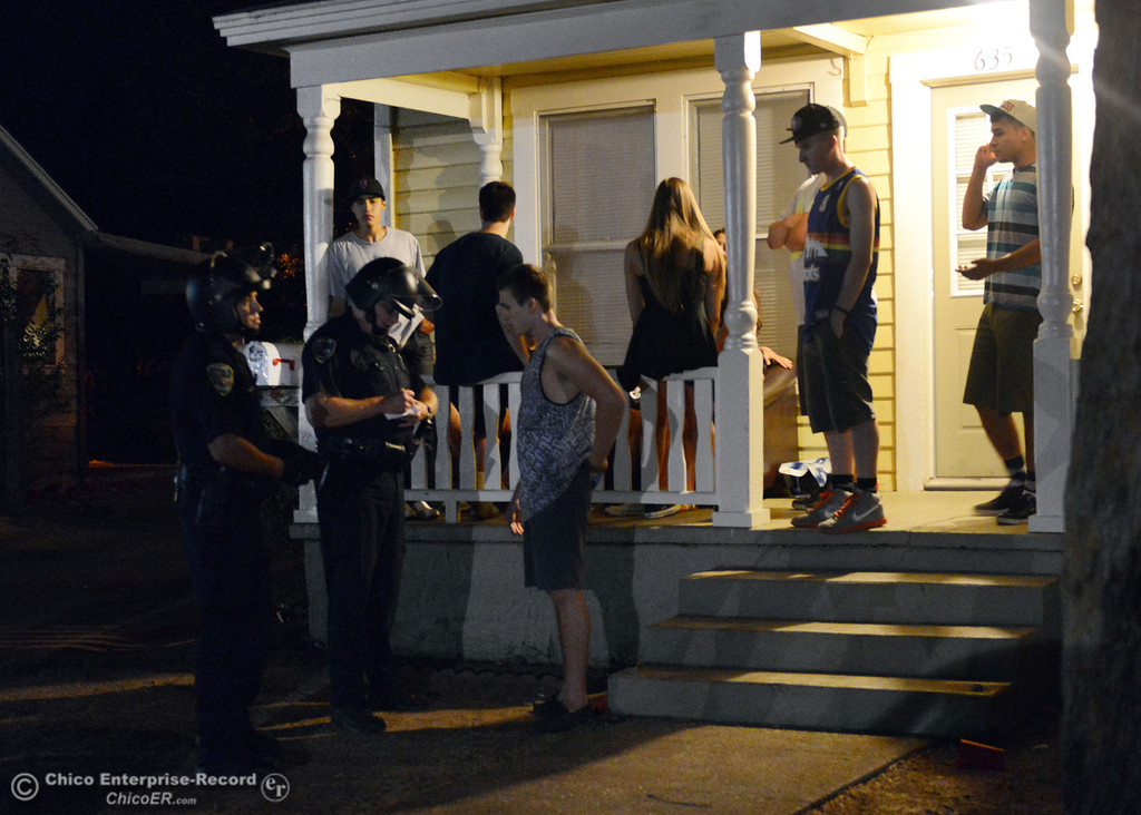 Description of . Chico Police talk to residents at 635 Ivy St. in the south campus area Friday, August 23, 2013 in Chico, Calif.  Police put on helmets after bottles were thrown at them.