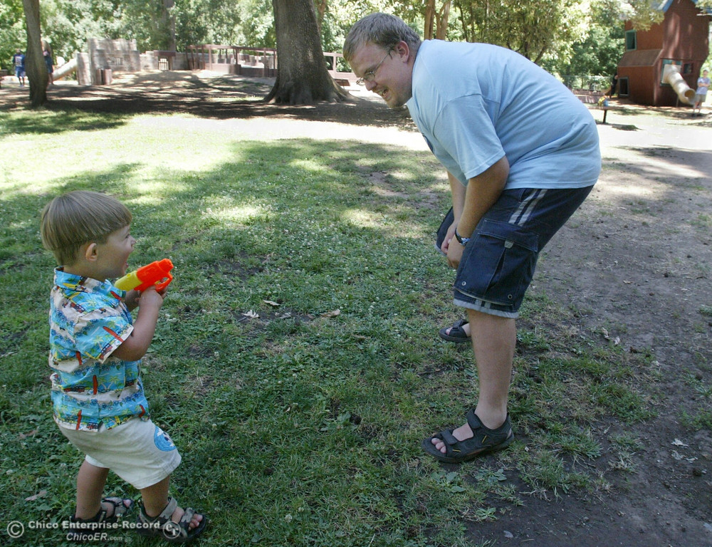 . Nathaniel Rupert, 2, snuck up on Bryan Rupert (right) and gave him a squirt from his water gun while they enjoyed each other at Caper Acres on Father\'s Day in this file photo from June 2004. (Ty Barbour/Chico Enterprise-Record file photo)
