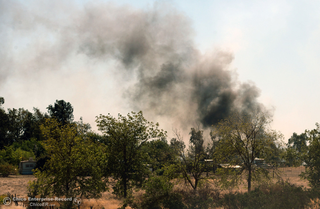 . Dark smoke rises from a fire that Oroville Fire, El Medio Fire, and Cal Fire - Butte County battle along Power House Hill Rd and Dad Lane that burned several structures and debris piles Thursday, September 26, 2013, in Oroville, Calif.  (Jason Halley/Chico Enterprise-Record)
