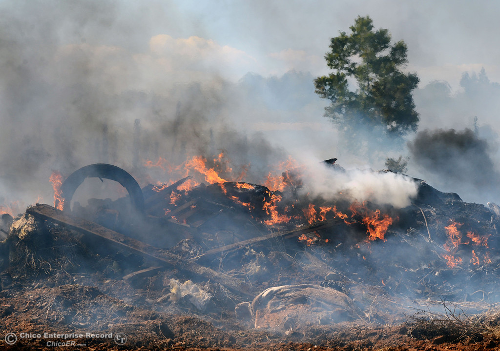 Description of . A debris pile burns as Oroville Fire, El Medio Fire, and Cal Fire - Butte County battle a fire along Power House Hill Rd and Dad Lane that burned several structures and debris piles Thursday, September 26, 2013, in Oroville, Calif.  (Jason Halley/Chico Enterprise-Record)