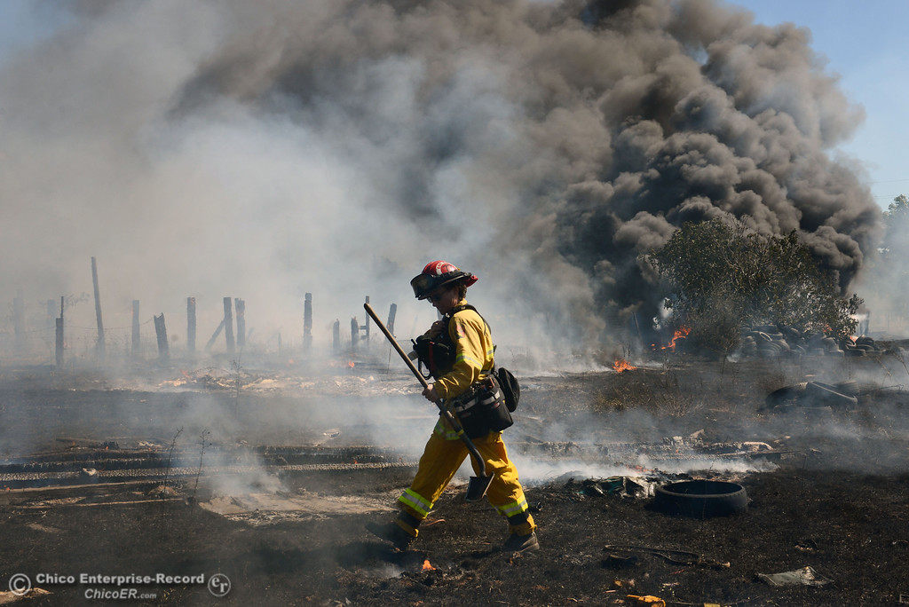 Description of . Cal Fire - Butte County Capt. Lydia Soileau with Oroville Fire and El Medio Fire battle a fire along Power House Hill Rd and Dad Lane that burned several structures and debris piles Thursday, September 26, 2013, in Oroville, Calif.  (Jason Halley/Chico Enterprise-Record)