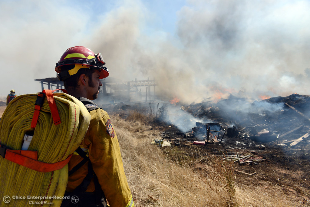 Description of . El Medio Fire Capt. Donald Robinson (left) with Oroville Fire, and Cal Fire - Butte County battle a fire along Power House Hill Rd and Dad Lane that burned several structures and debris piles Thursday, September 26, 2013, in Oroville, Calif.  (Jason Halley/Chico Enterprise-Record)