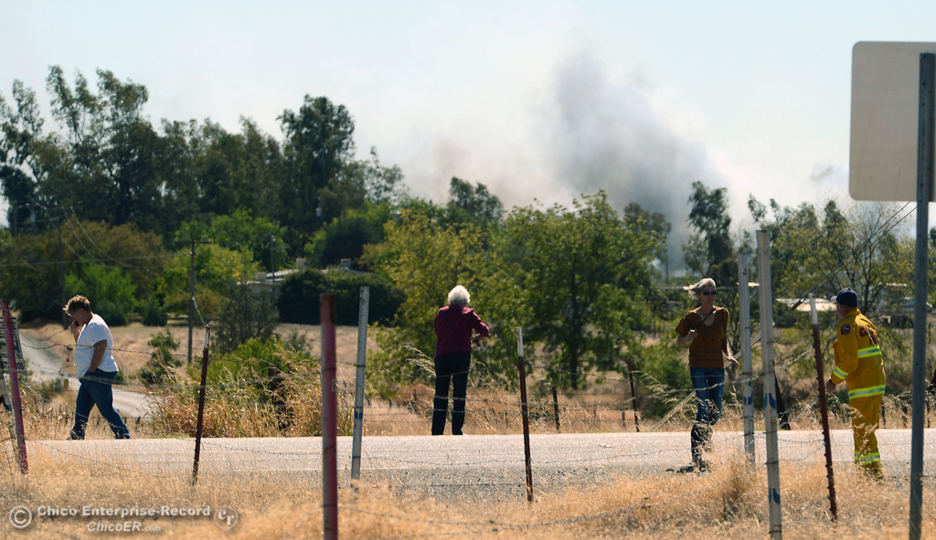 Description of . People stand along E. Palermo St. to watch Oroville Fire, El Medio Fire, and Cal Fire - Butte County battle a fire along Power House Hill Rd and Dad Lane that burned several structures and debris piles Thursday, September 26, 2013, in Oroville, Calif.  (Jason Halley/Chico Enterprise-Record)