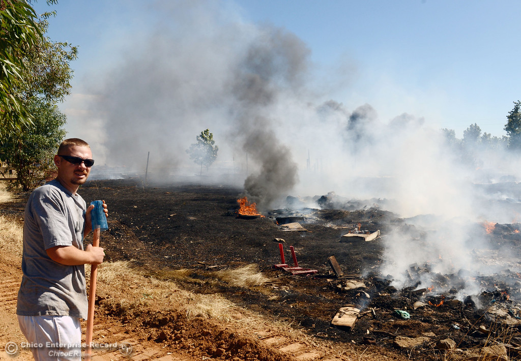 . A nearby resident stands watching Oroville Fire, El Medio Fire, and Cal Fire - Butte County battle a fire along Power House Hill Rd and Dad Lane that burned several structures and debris piles Thursday, September 26, 2013, in Oroville, Calif.  (Jason Halley/Chico Enterprise-Record)