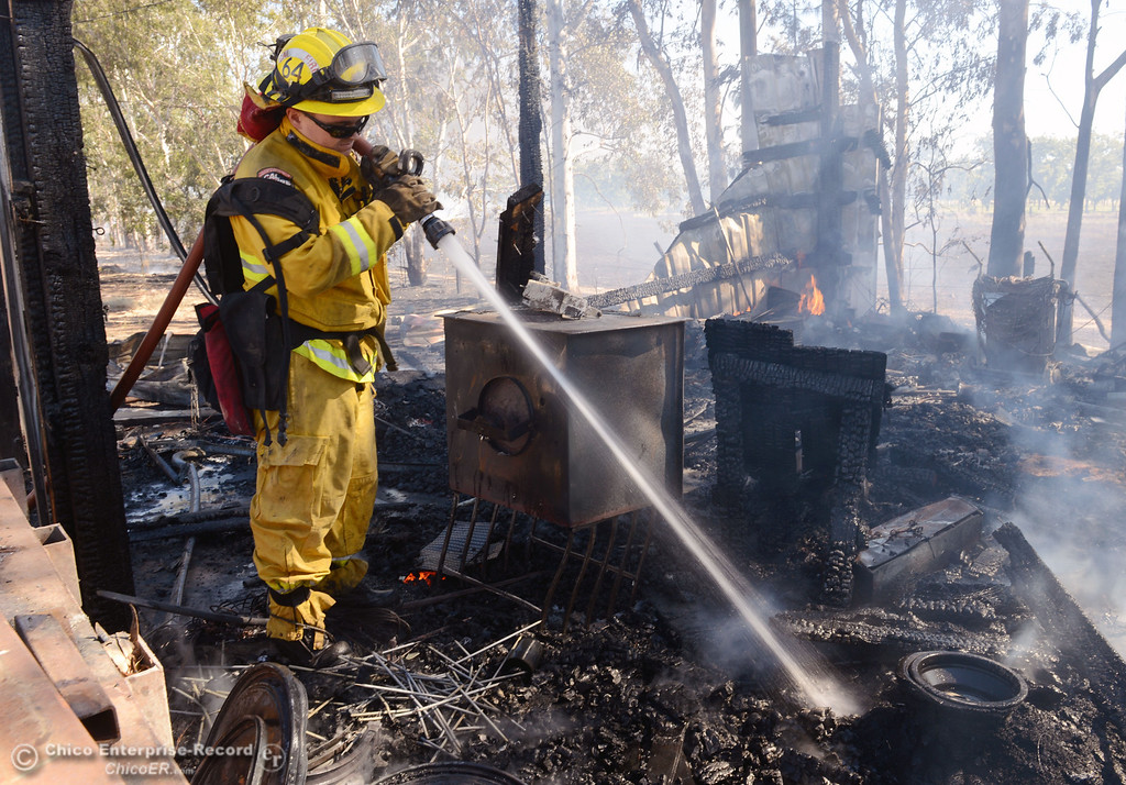 Description of . Cal Fire - Butte County Nathan Daniels hoses hot spots on a strucutre that Oroville Fire, El Medio Fire battled along Power House Hill Rd and Dad Lane that burned several structures and debris piles Thursday, September 26, 2013, in Oroville, Calif.  (Jason Halley/Chico Enterprise-Record)