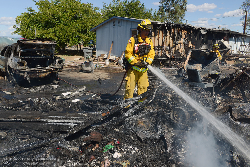 Description of . Cal Fire - Butte County Kyle Mallinger hoses hot spots on a structure that Oroville Fire, El Medio Fire battled along Power House Hill Rd and Dad Lane that burned several structures and debris piles Thursday, September 26, 2013, in Oroville, Calif.  (Jason Halley/Chico Enterprise-Record)
