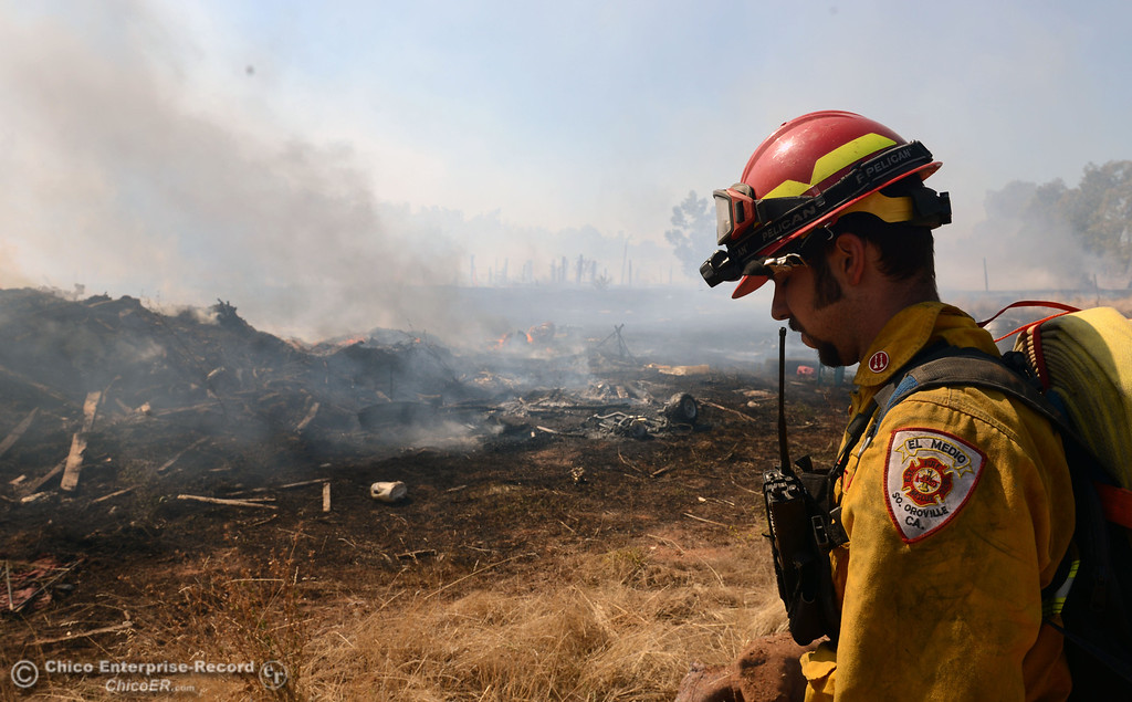 Description of . El Medio Fire Capt. Donald Robinson with Oroville Fire, and Cal Fire - Butte County battle a fire along Power House Hill Rd and Dad Lane that burned several structures and debris piles Thursday, September 26, 2013, in Oroville, Calif.  (Jason Halley/Chico Enterprise-Record)