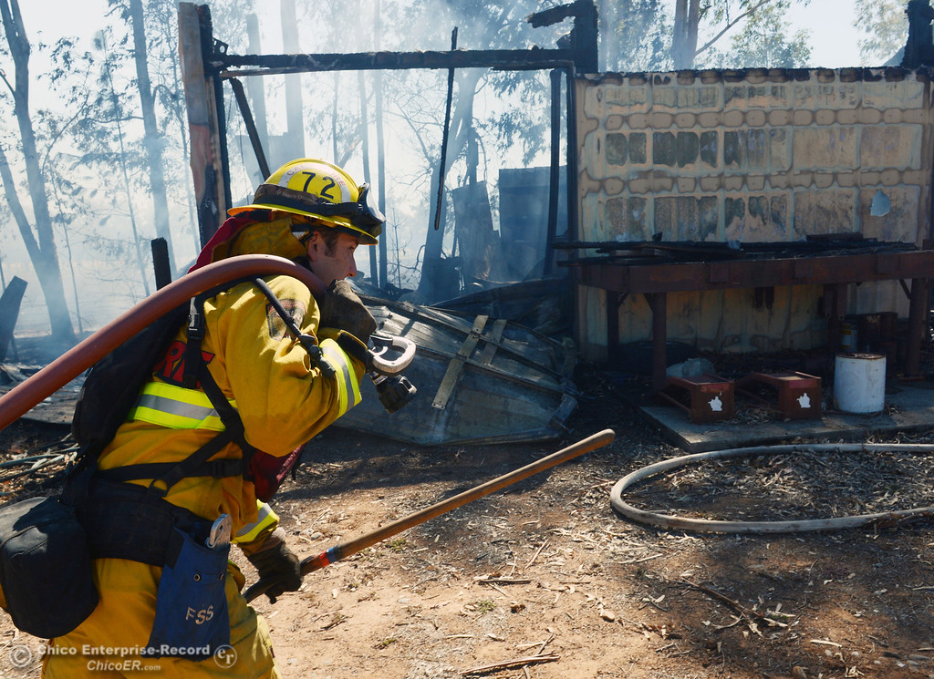 . Cal Fire - Butte County Clint Siebert carries a hose line as Oroville Fire and El Medio Fire battle a fire along Power House Hill Rd and Dad Lane that burned several structures and debris piles Thursday, September 26, 2013, in Oroville, Calif.  (Jason Halley/Chico Enterprise-Record)