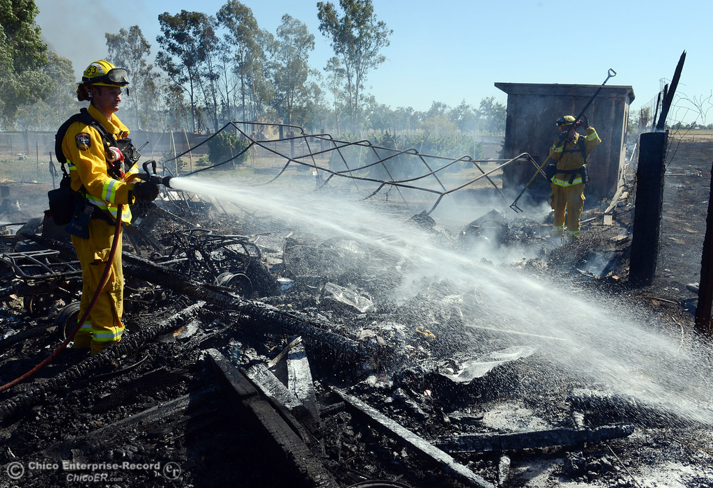 . Cal Fire - Butte County Kyle Mallinger hoses hot spots on a structure that Oroville Fire, El Medio Fire battled along Power House Hill Rd and Dad Lane that burned several structures and debris piles Thursday, September 26, 2013, in Oroville, Calif.  (Jason Halley/Chico Enterprise-Record)