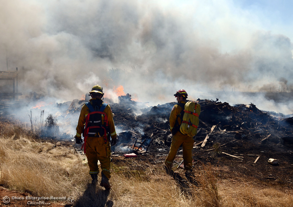 Description of . El Medio firefighter Chris Lewis (left) and Capt. Donald Robinson (right) with Oroville Fire, and Cal Fire - Butte County battle a fire along Power House Hill Rd and Dad Lane that burned several structures and debris piles Thursday, September 26, 2013, in Oroville, Calif.  (Jason Halley/Chico Enterprise-Record)