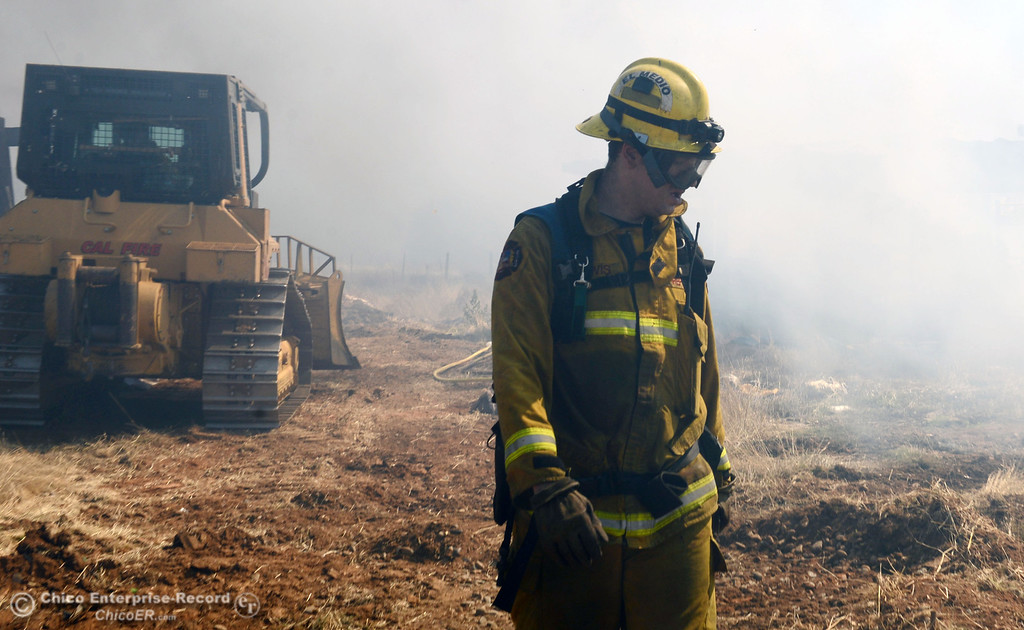 Description of . El Medio firefighter Chris Lewis (right) with Oroville Fire, and Cal Fire - Butte County battle a fire along Power House Hill Rd and Dad Lane that burned several structures and debris piles Thursday, September 26, 2013, in Oroville, Calif.  (Jason Halley/Chico Enterprise-Record)