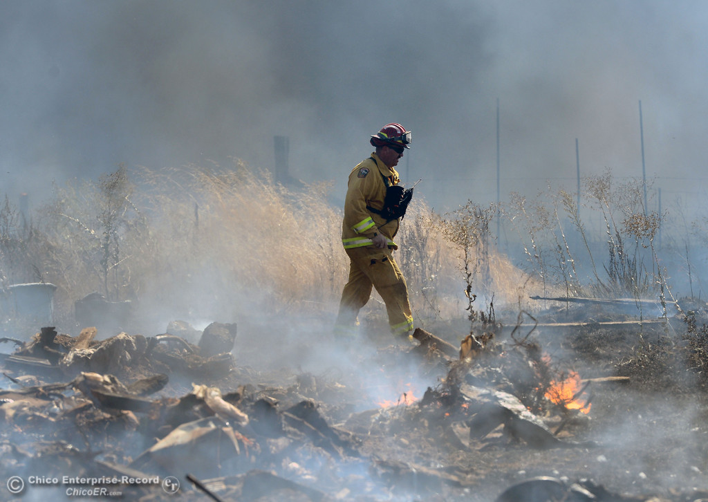 Description of . Cal Fire-Butte County Capt. Tony Brownell walks through smoke as Oroville Fire and El Medio Fire battle a fire along Power House Hill Rd and Dad Lane that burned several structures and debris piles Thursday, September 26, 2013, in Oroville, Calif.  (Jason Halley/Chico Enterprise-Record)