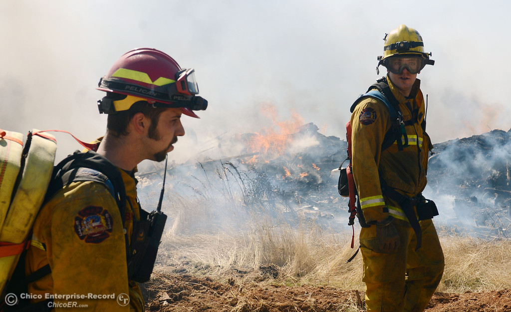 Description of . El Medio Fire Capt. Donald Robinson (left) and firefighter Chris Lewis (right) with Oroville Fire, and Cal Fire - Butte County battle a fire along Power House Hill Rd and Dad Lane that burned several structures and debris piles Thursday, September 26, 2013, in Oroville, Calif.  (Jason Halley/Chico Enterprise-Record)