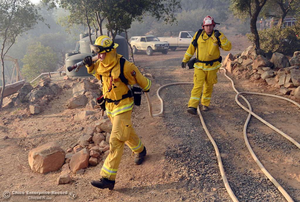 Description of . Cal Fire firefighter engineer Troy Hand Capt. Russ Palamaryuk carries a hose line to protect a structure threatened by the Swedes Fire that burned along Swedes Flat Road, in the vicinity of Chinese Wall Road, just east or Oro Bangor Highway Friday, August 16, 2013 in Oroville, Calif. Over 200 acres were burned with at least one structure lost. (Jason Halley/Chico Enterprise-Record)