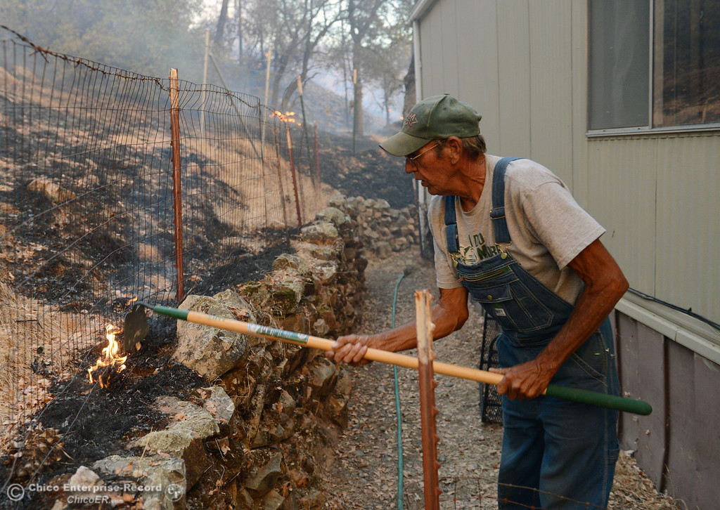 Description of . Glenn Bentley puts out hotspots as the flames reached close to his home along Chinese Wall Road as the Swedes Fire burned along Swedes Flat Road, in the vicinity of Chinese Wall Road, just east or Oro Bangor Highway Friday, August 16, 2013 in Oroville, Calif. Over 200 acres were burned with at least one structure lost. (Jason Halley/Chico Enterprise-Record)