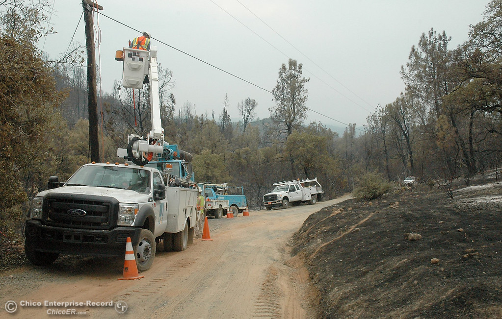 Description of . PG&E crews work on a burned tap line and replace poles  Monday on Chinese Wall Road, off Swedes Flat Road.  Swedes Fire Monday, Aug. 19, 2013.  (Barbara Arrigoni/Staff Photo)