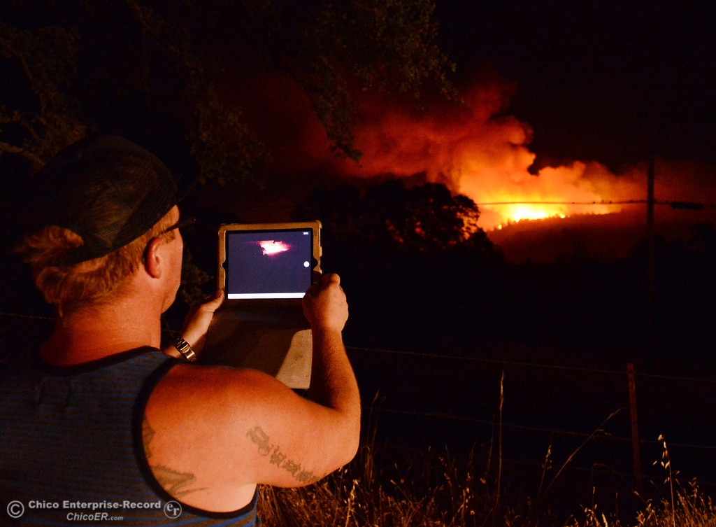 Description of . Jordan Perkins take a photo on his iPad of the Swedes Fire that burns into the night as seen from Oro Bangor Highway, in the vicinity of Chinese Wall Road and Swedes Flat Road Friday, August 16, 2013 in Oroville, Calif. Over 200 acres were burned with at least one structure lost. (Jason Halley/Chico Enterprise-Record)