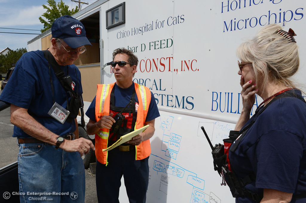 Description of . North Valley Animal Disaster Group David Bequette, John Maretti, and Sandy Doolittle (left to right) coordinate a horse rescue at a home under mandatory evacuation areas around the Swedes Fire southeast of Oroville that were expanded just after noon Saturday, August 17, 2013 in Oroville, Calif.  (Jason Halley/Chico Enterprise-Record)