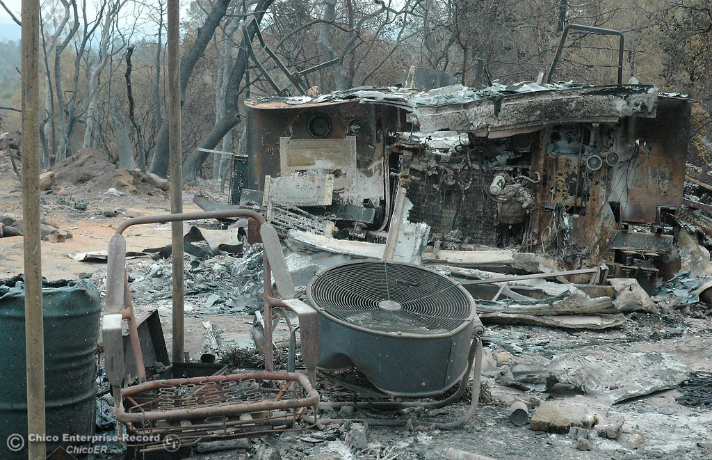 Description of . A chair, fan and burned out truck remain Monday on property at Chinese Wall Road, below a residence destroyed in the Swedes Fire.  Monday, Aug. 19, 2013.  (Barbara Arrigoni/Staff Photo)