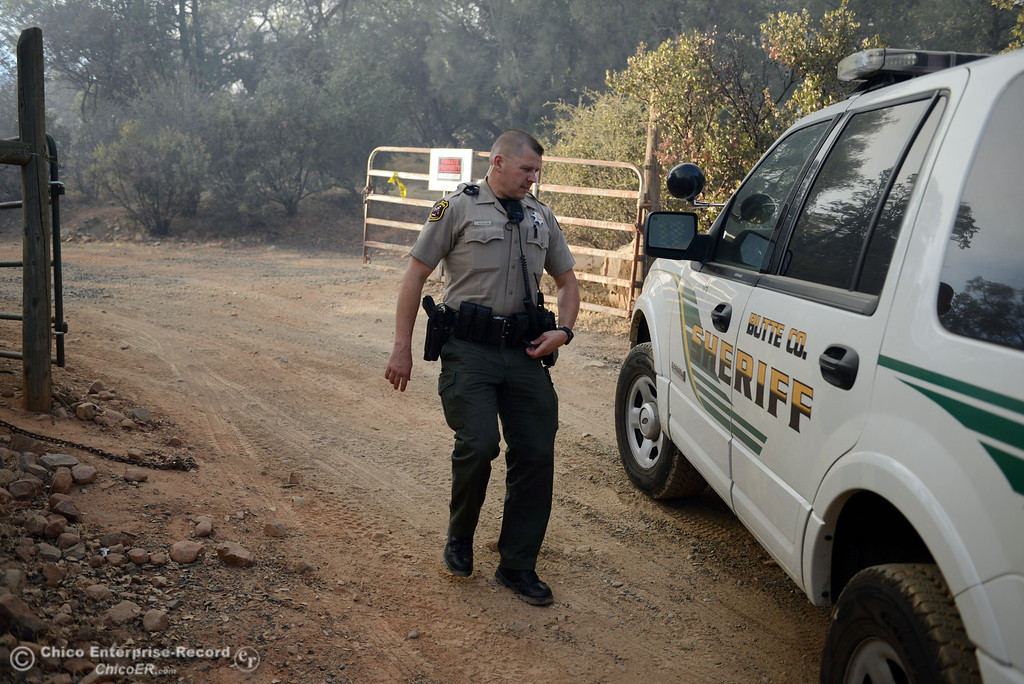 Description of . Butte County Sheriff Deputy J. Nicholaw checks homes in the vicinity of Chinese Wall Road as the Swedes Fire burned along Swedes Flat Road, just east or Oro Bangor Highway Friday, August 16, 2013 in Oroville, Calif. Over 200 acres were burned with at least one structure lost. (Jason Halley/Chico Enterprise-Record)
