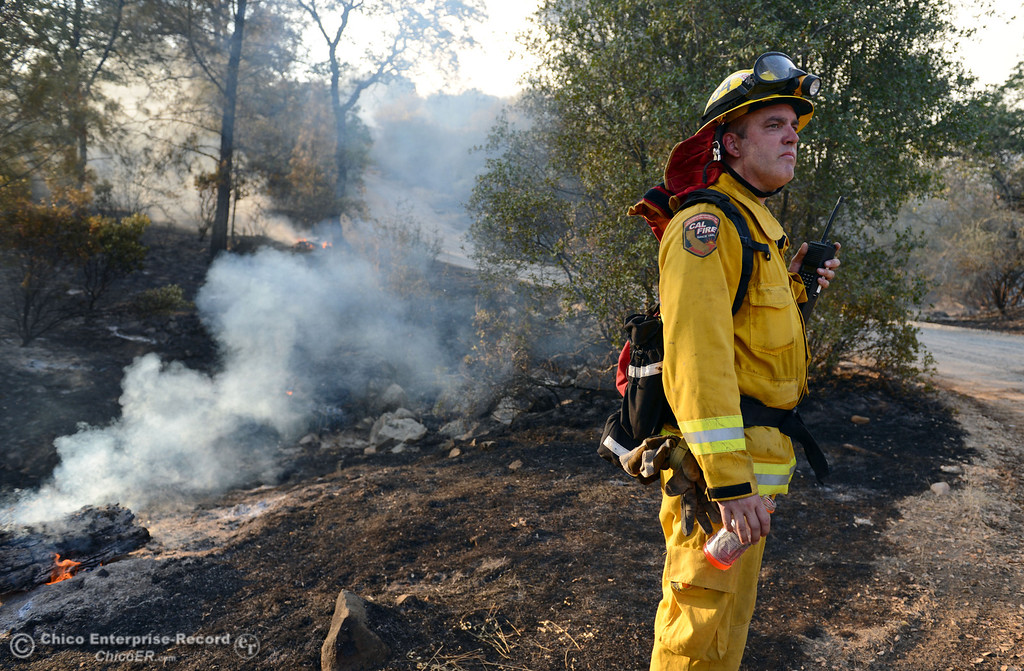 Description of . Cal Fire firefighter Dave Steed looks on along Chinese Wall Rd. as the Swedes Fire burned along Swedes Flat Road, in the vicinity of Chinese Wall Road, just east or Oro Bangor Highway Friday, August 16, 2013 in Oroville, Calif. Over 200 acres were burned with at least one structure lost. (Jason Halley/Chico Enterprise-Record)