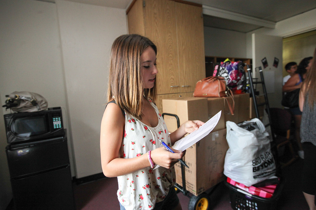 Description of . Cassidy Pierce,  goes through a University Housing check list before she begins to put all of her things away in her new room in Whitney Hall at Chico State on Tuesday, August 20, 2013. (Frank Rebelo/Staff Photo)