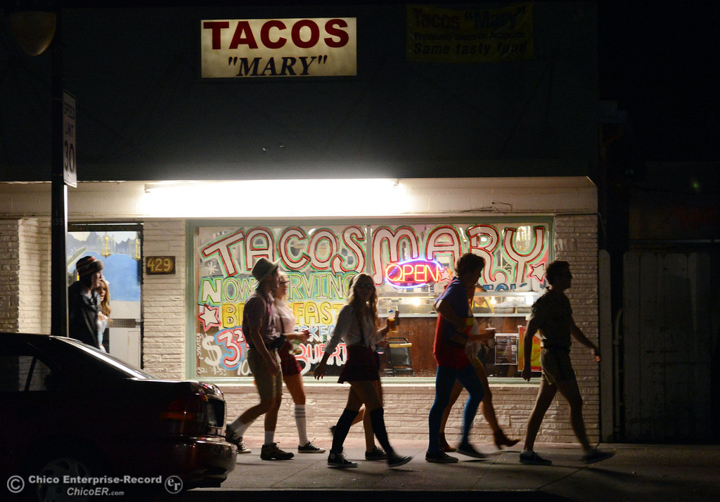 Description of . Costumed crowds walk past Tacos Mary through the streets of downtown and south Chico State campus for Halloween Thursday, October 31, 2013 in Chico, Calif.  (Jason Halley/Chico Enterprise-Record)