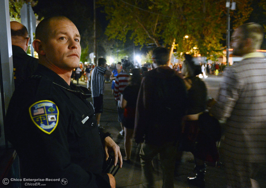 Description of . Chico Police officer Mike Caldwell patrols 5th Street and Ivy Street as costumed crowds walk the through the streets of downtown and south Chico State campus area for Halloween Thursday, October 31, 2013 in Chico, Calif.  (Jason Halley/Chico Enterprise-Record)