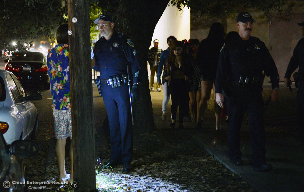 . Chico police Sgt. Curtis Prosise (center) checks a beverage container of an individual while on patrol the through the streets of downtown and south Chico State campus area for Halloween Thursday, October 31, 2013 in Chico, Calif.  (Jason Halley/Chico Enterprise-Record)