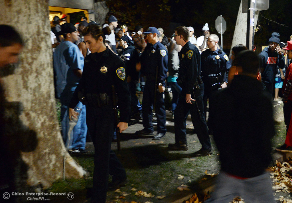 Description of . Chico police officer Regan Ortega (left) pours out a glass bottle of alcohol as they patrol the through the streets of downtown and south Chico State campus area for Halloween Thursday, October 31, 2013 in Chico, Calif.  (Jason Halley/Chico Enterprise-Record)
