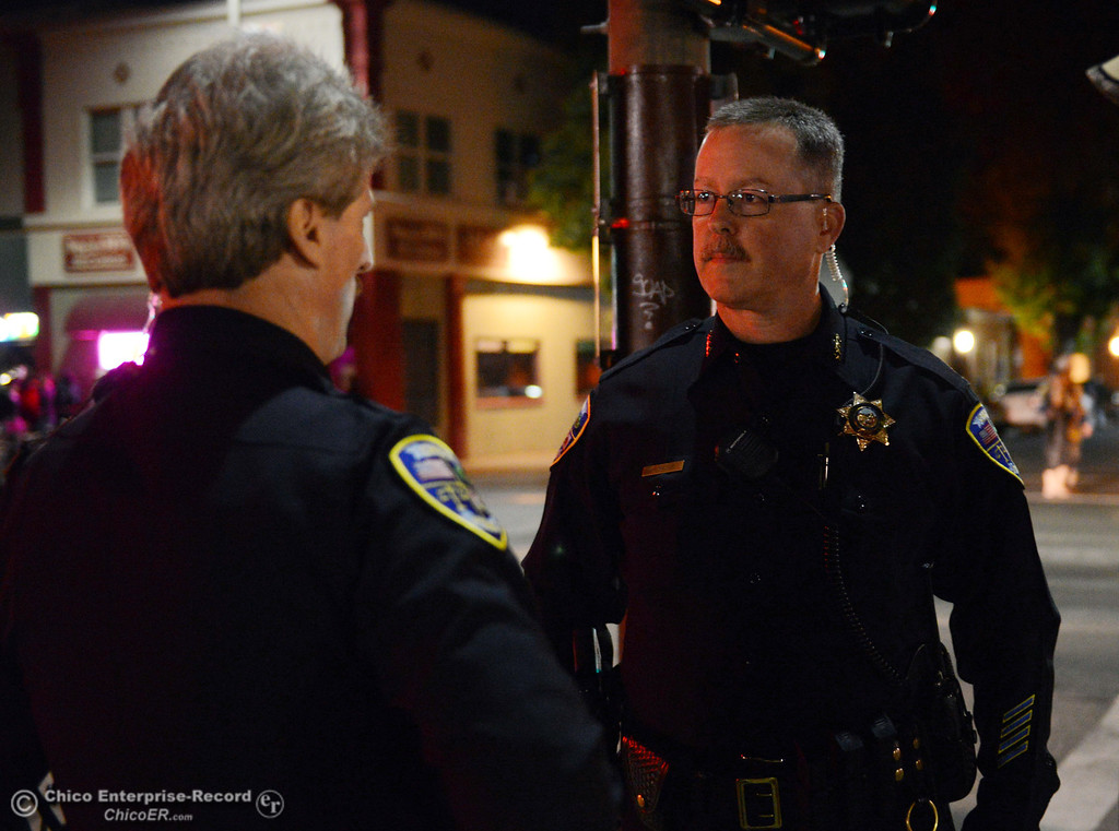 Description of . Chico Police Sgt. George Laver (left) and Chief Kirk Trostle (right) patrol the through the streets of downtown and south Chico State campus area for Halloween Thursday, October 31, 2013 in Chico, Calif.  (Jason Halley/Chico Enterprise-Record)