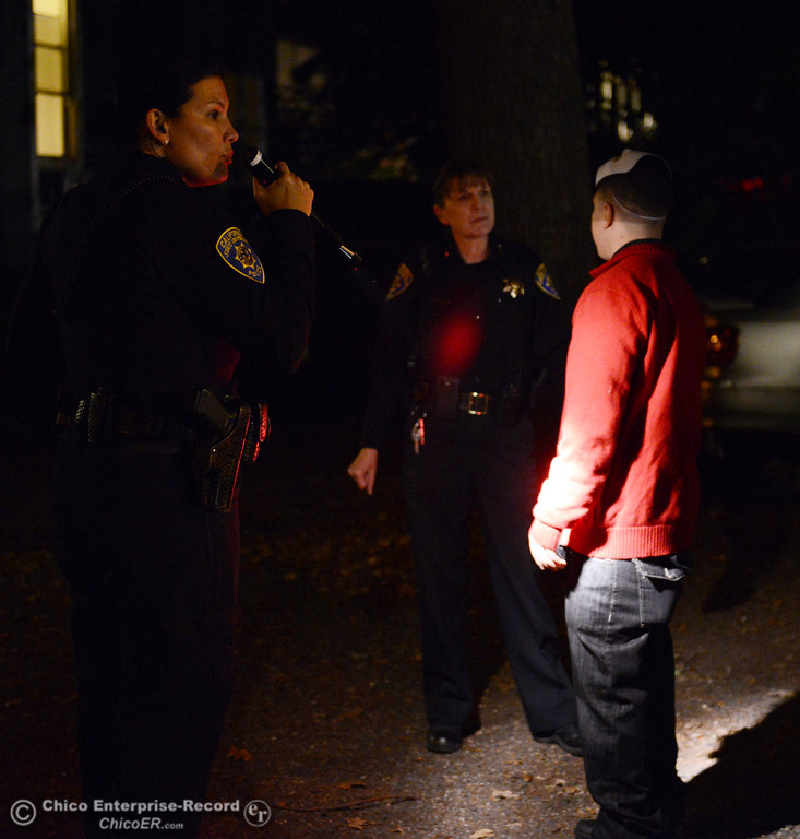Description of . Chico State Police Lt. Corinne Beck (left) and Chief Robyn Hearne (center) talk to an invdividual as they patrol the through the streets of downtown and south Chico State campus area for Halloween Thursday, October 31, 2013 in Chico, Calif.  (Jason Halley/Chico Enterprise-Record)