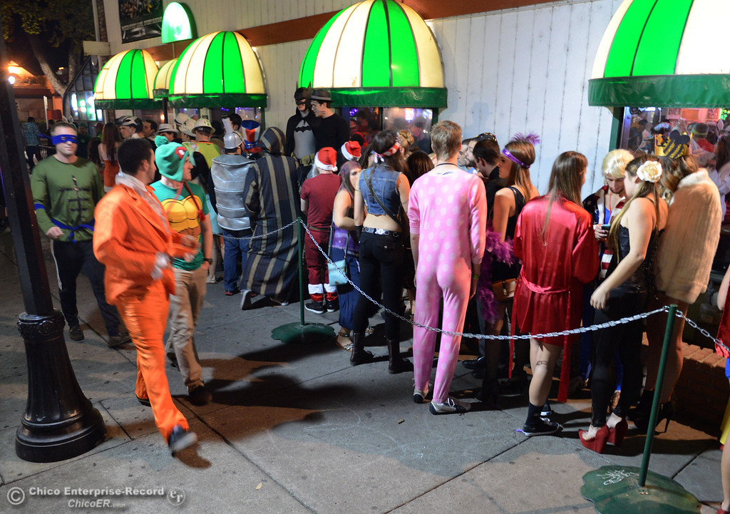 Description of . Costumed crowds wait in line at Riley's Bar as others walk through the streets of downtown and south Chico State campus for Halloween Thursday, October 31, 2013 in Chico, Calif.  (Jason Halley/Chico Enterprise-Record)