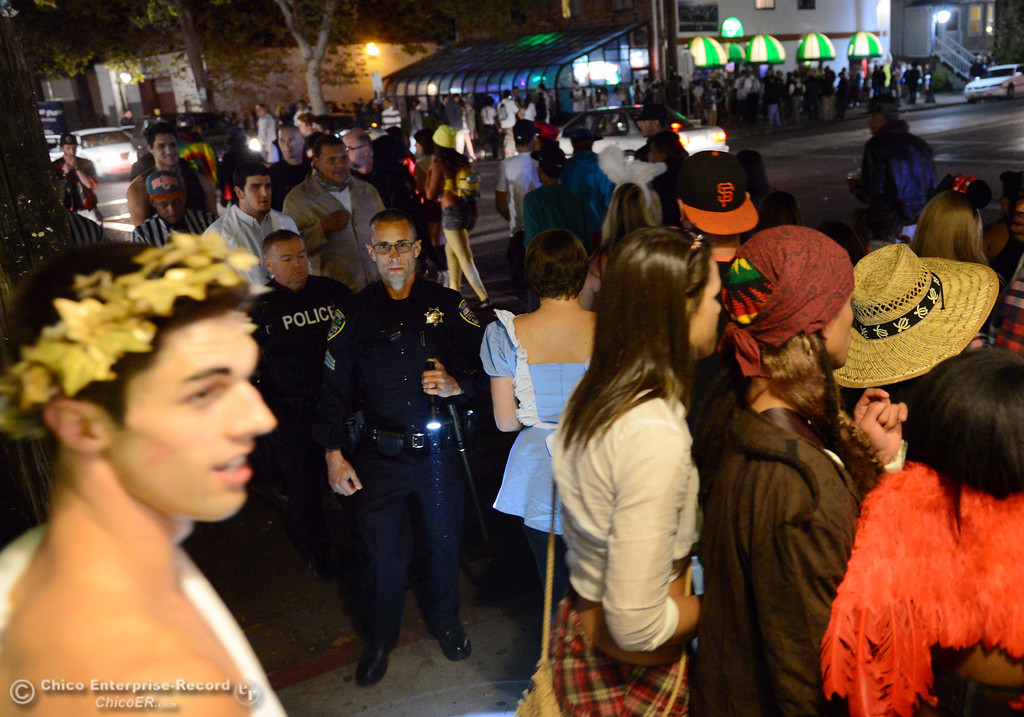 Description of . Chico Police Sgt. Scott Zuschin (center) keeps an eye on the costumed crowd that walk through the 5th Street and Ivy Street in downtown and south Chico State campus area for Halloween Thursday, October 31, 2013 in Chico, Calif.  (Jason Halley/Chico Enterprise-Record)