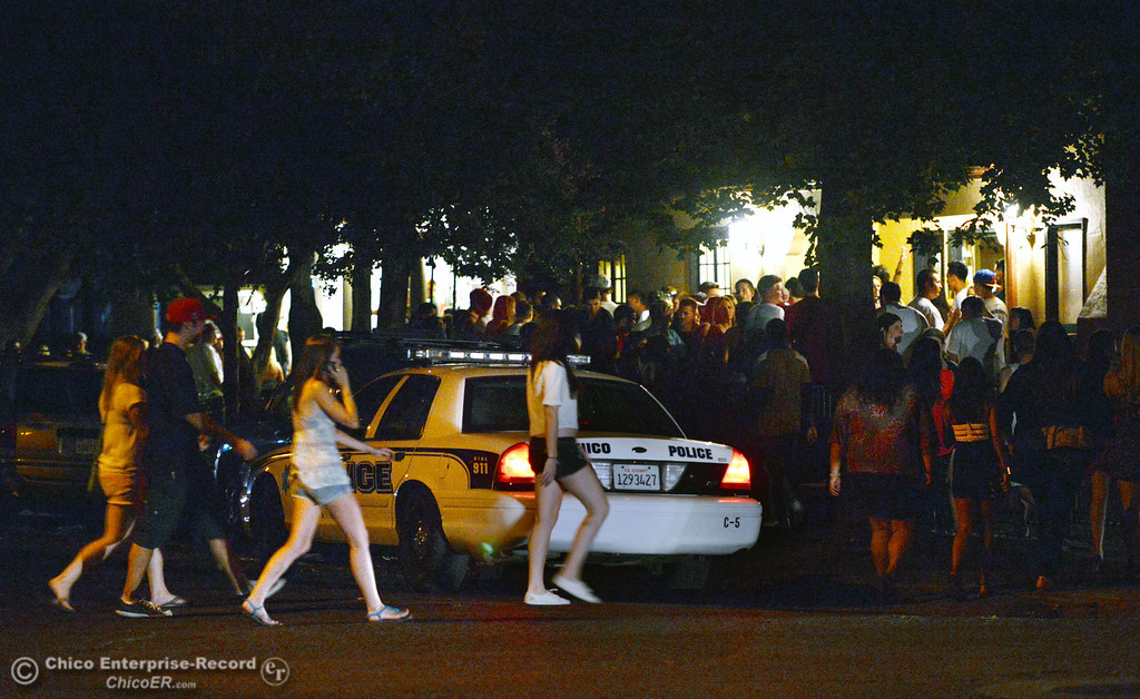 Description of . People walk past a police car on 4th Street and Hazel Street near a party as the south campus area was fairly quiet before Labor Day weekend starting Friday, August 30, 2013 in Chico, Calif.  (Jason Halley/Chico Enterprise-Record)