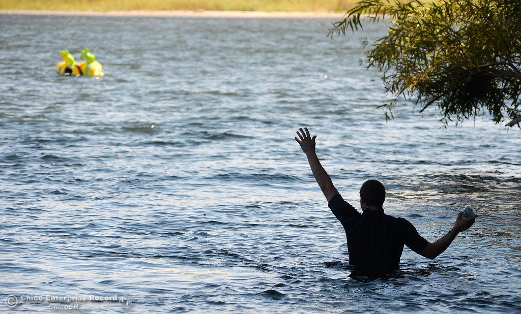 Description of . A stranded tuber waves to his friends after his floatation device got away from him on the Sacramento River between the Irvine Finch boat Launch and Pine Creek near Scotty\'s Boat Landing in celebration of Labor Day Monday, Sept. 2, 2013. (Bill Husa/Staff Photo)