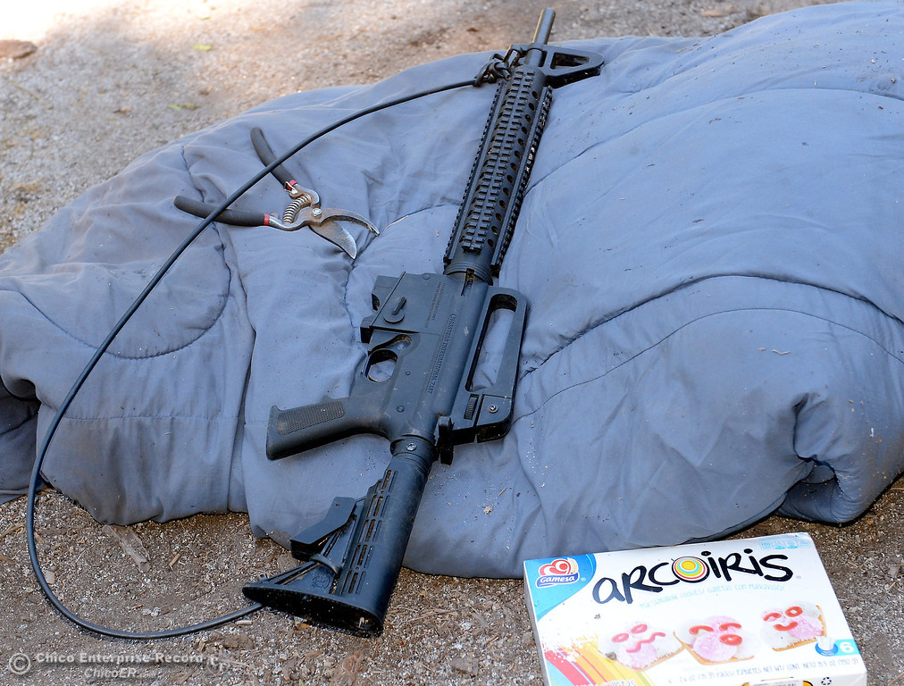 Description of . This .22 caliber semi-automatic rifle and a box of cookies were found in an elevated and camoflaged platform near the grow area as several members of a multi agency Special Enforcement Unit eradicated nearly 7,300 marijuana plants from a remote area in Upper Concow Thursday, Aug. 15, 2013. A strap made of water line tubing is attached to the gun to help the user carry it. Two suspects were arrested in the marijuana garden. (Bill Husa/Staff Photo)