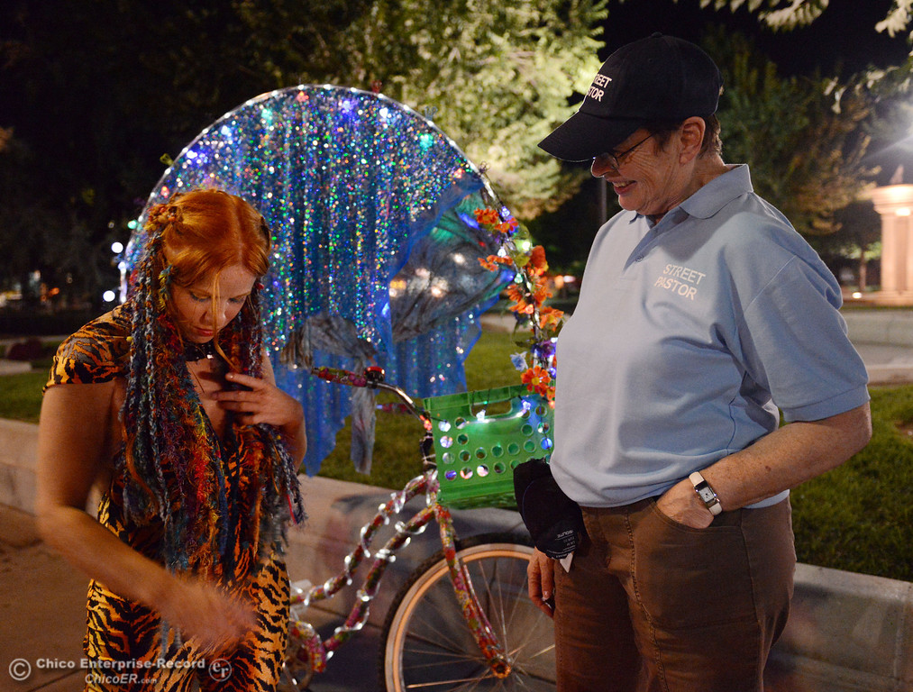 Description of . Kelly Mosenfelder created a colorful light bike for burning man that she test rode around downtown as she talks with Nancy Calkins (right), that was part of the Street Pastors program Friday, August 23, 2013 in Chico, Calif.  (Jason Halley/Chico Enterprise-Record)