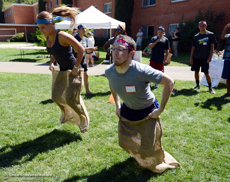 Description of . Chico State students Madison Hossfeld, 18 (left) races Taylor Moffitt, 21 (right) in a sack race as an alternative activity to floating on the Sacramento River for Labor Day at the Wildcat Challenge event on the lawn between Lassen Hall and Sutter Hall on the Chico State Campus Saturday, August 31, 2013 in Chico, Calif.  (Jason Halley/Chico Enterprise-Record)