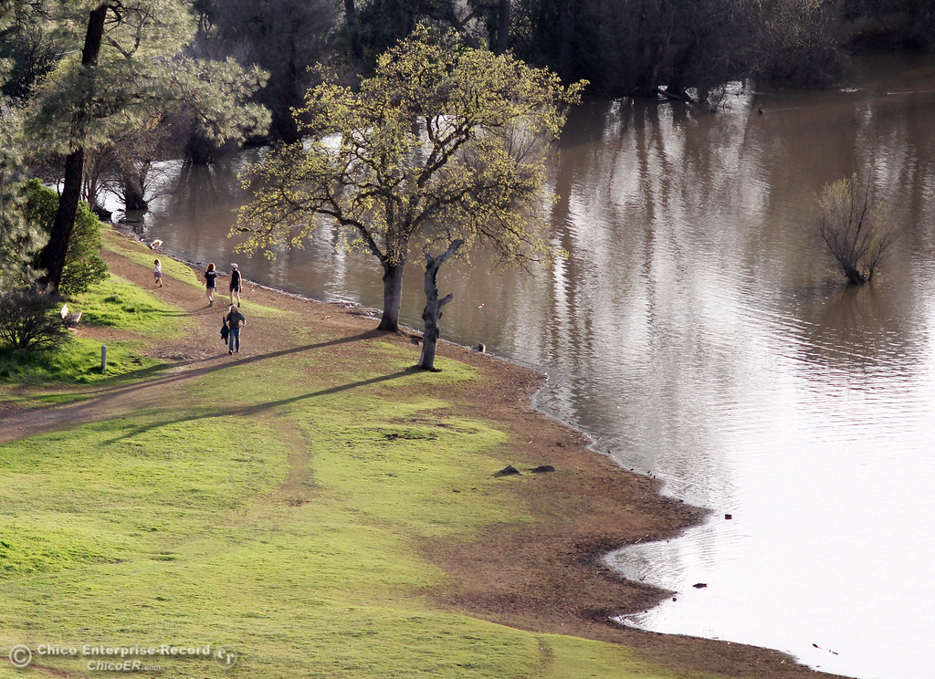 Description of . Hikers and their dogs walk past along a trail past Horseshoe Lake as people enjoy the warm weather in upper Bidwell Park on March 13, 2013 in Chico, Calif. (Jason Halley/Chico Enterprise-Record)