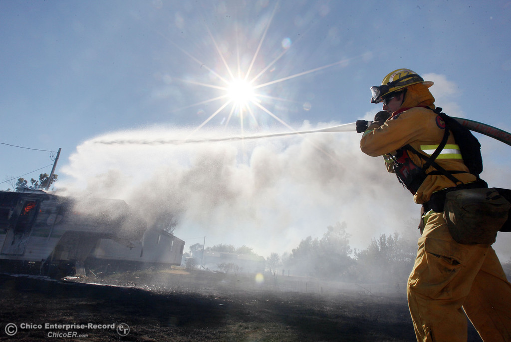 Description of . Cal Fire - Butte County firefighter Clint Siebert hoses a trailer on fire as they battle a vegetation fire off Vineyard Lane Friday, July 12, 2013 in Oroville, Calif.  (Jason Halley/Chico Enterprise-Record)