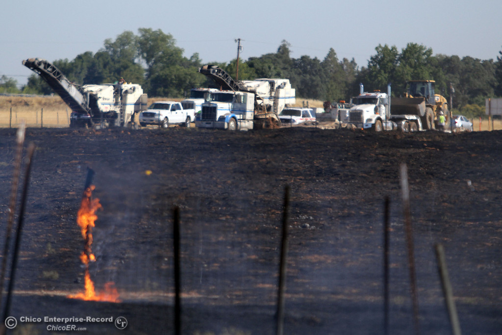 Description of . Cal Trans equipment rests along Hwy 70 near the start of the fire as Cal Fire - Butte County firefighters battle a fire off Vineyard Lane Friday, July 12, 2013 in Oroville, Calif.  (Jason Halley/Chico Enterprise-Record)