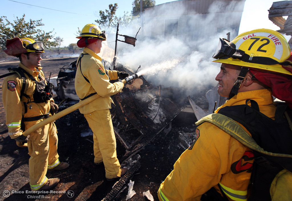 Description of . Cal Fire - Butte County firefighters Brad Padilla, Ibe Liebenberg, and Mike Lamonica (left to right) battle a fire burning a trailer off Vineyard Lane Friday, July 12, 2013 in Oroville, Calif.  (Jason Halley/Chico Enterprise-Record)
